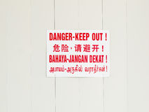 Danger and keep out sign. Board on hoarding outside construction site in four languages - English, Chinese, Tamil and Malay stock photography