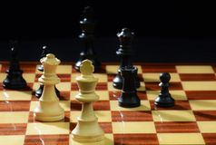 Danger lurking in the shadows!  Chess game in play. Stock Photo