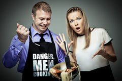Danger, men cooking. Man cooking some strange things and his wife is shocked Stock Images