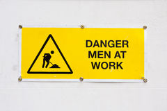 Danger men at work. Warning sign to tell people of men working Stock Photos