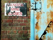 Danger mine gases. A warning notice in peeling red and white paint fastened to a red brick wall next to a corroding steel door painted blue Royalty Free Stock Photo