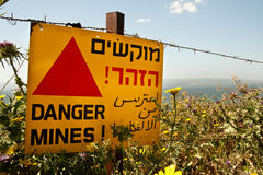 Danger mines!. A sign reading Danger Mines! hangs from a barbed wire fence in the Golan Heights. Effectively annexed by Israel in 1981, the Golan is still Royalty Free Stock Images