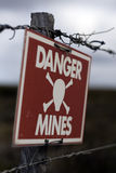 Danger mines sign. Red danger mines sign on barbed wire fence Royalty Free Stock Photo