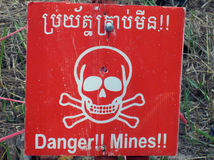 Danger Mines signal. In Cambodia along the road beside an uncleared field Stock Photos