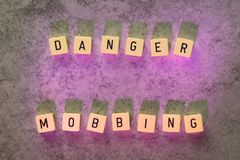 Danger Mobbing text on grey dabbled stone background Royalty Free Stock Photography