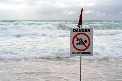 DANGER! no swimming. Warning sign with stormy ocean behind Stock Photos