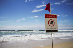 Danger no swimming horizontal. Rough surf beach at surfers paradise australia with danger sign Royalty Free Stock Photography