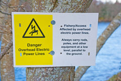 Danger notice for fishermen. An image of a warning notice fixed to a tree beside a river reminding fishermen of overhead electric power cables and the danger if stock illustration