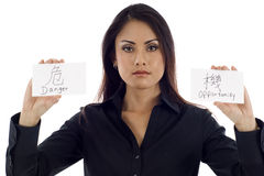 Danger & Opportunity. Investment Concept: Asian businesswoman holding 2 cards - Danger & Opportunity Stock Images