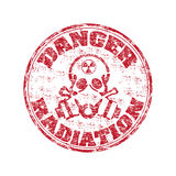 Danger radiation stamp. Red grunge rubber stamp with skull wearing a gas mask and the radiation symbol on the top of his head. Danger radiation grunge rubber Royalty Free Stock Photo