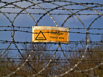 Danger razor wire. Danger sign on a razor wire fence Stock Photos