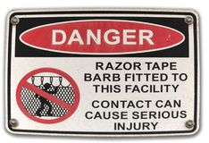 Danger Razor Wire signage. Warning about razor tape barb wire fitted to fence Royalty Free Stock Photo