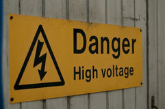 Danger. Rectangular yellow sign with warning symbol reading 'Danger High Voltage' nailed to a wooden gate Stock Images