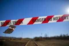 Danger red and white tape barricade exclusion zone area with written authorised personnel entry only on train track royalty free stock image