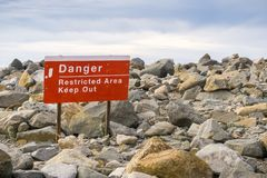 'Danger Restricted Area Keep Out ' sign posted on the shoreline of the Pacific Ocean on a jetty closed to the public, Morro Bay,. California stock images