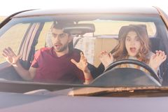 Danger on road. Mad young woman and man have car crash, looks in terror in windscreen. Depressed female can`t control movement and. Danger on road. Mad young Stock Image