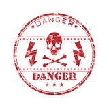Danger rubber stamp. Abstract red rubber office stamp with crossbones, electricity symbols and the word danger written inside the stamp Royalty Free Stock Photo