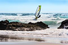 Danger seeker. Windsurfer on a wave close to the beach, aiming at a small gap between rocks royalty free stock photo