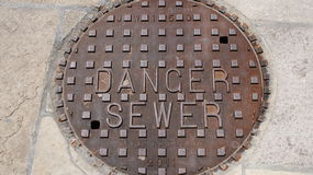 `Danger Sewer` sidewalk utility cover - manhold cover Royalty Free Stock Photos