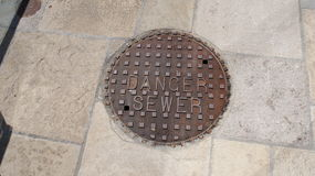`Danger Sewer` utility sidewalk cover manhole cover Stock Photography
