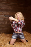 Danger sexy woman with revolver over pile of straw texture backg Stock Photos