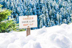 Danger sheer cliff keep off sign on the edge of land cover with snow. Royalty Free Stock Images