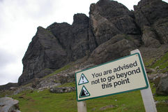 Danger sign. A sign reading, you are advised not to go beyond this point looking up steep mountain cliffs stock photos