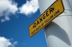 Danger sign. Yellow danger sign backed by deep blue skies Stock Images