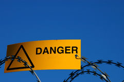 Danger sign. A danger sign on some razor wire, with blank space for extra text Royalty Free Stock Photo