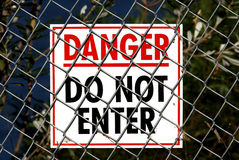Danger Sign. White sign with Red and Black writing saying Danger Do Not Enter and attached to a wire fence Royalty Free Stock Photography