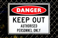 Danger sign. A red, white and black danger sign attached to a wire fence Royalty Free Stock Images