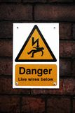 Danger sign on a brick wall. A yellow electrical danger sign on a red brick wall Stock Photography