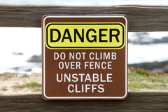 Danger sign on cliff over beach Royalty Free Stock Images