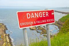 Danger sign on cliff top. Red danger sign on cliff top with text ' danger erosion and falling rocks ' with background of sea and historic pier Royalty Free Stock Image