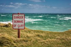 New Zealand coast. Danger sign at coast with huge waves near Bluff, New Zealand Stock Photography