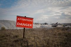 Danger sign in front of industrial area. Red danger sign in front of industrial area with mining machinery working in the field royalty free stock photography