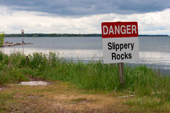 Danger Sign in Grass on the Lakeshore Royalty Free Stock Image