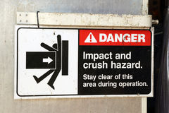 Danger Sign. Impact and Crush Hazard Danger Sign hanging on a factory door royalty free stock photos