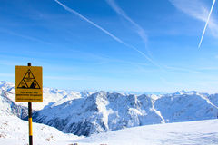 Danger sign in Mountains. Danger sign Hight mountains under blue sky beautiful winter panorama Stock Image