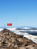 Danger Sign Ocean Waves. A red and white sign posting Danger on rock breakwater with large waves coming into Harbor mouth of Southern California Channel Islands Royalty Free Stock Photo