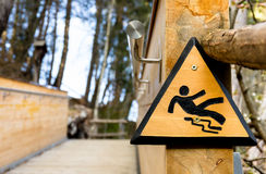 Slippery when wet - Wooden Sign in the Park. Danger sign in a park near the Dolomites in Italy Royalty Free Stock Photo