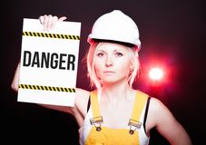 Danger sign placed on information board, worker woman Stock Images