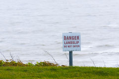 Danger sign for public information sign next to sea cliff Stock Photography