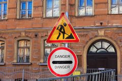 Signs informing about repair work and danger during street repair. Danger sign and roadworks against the backdrop of a European old building. road repair in the stock image