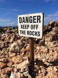 Danger sign. On a rocky beach Royalty Free Stock Image