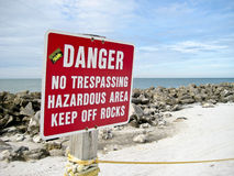 Danger Sign. A danger sign on a rocky beach, which says Danger No Trespassing Hazardous Area Keep off Rocks Stock Photos