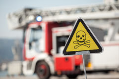 Danger sign with skull and crossbones, fire truck on background Royalty Free Stock Images