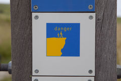 Danger sign on steep coast near Wissant. City at Nord-Pas-de-Calais region, France Royalty Free Stock Image