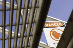Danger sign viewed from under stairs. A danger sign as viewed from under the stairs Royalty Free Stock Images