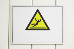 Danger sign warn, slippery surface. Triangle shaped yellow notice board on wall Stock Photo